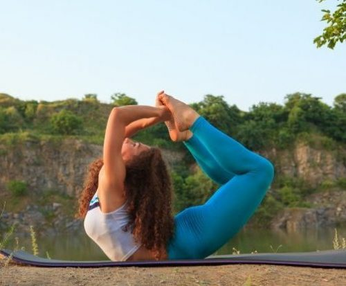 young woman is practicing yoga near river 155003 4424 e1587123348807