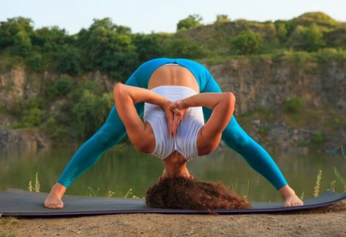 young woman is practicing yoga near river 155003 4425 e1587124253593